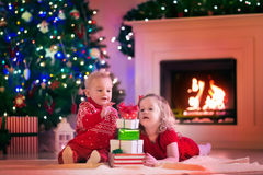 Kids opening Christmas presents at fire place. Family on Christmas eve at fireplace. Kids opening Xmas presents. Children under Christmas tree with gift boxes royalty free stock photo