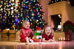 Kids opening Christmas presents at fireplace Stock Image