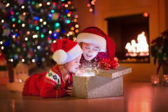 Kids opening Christmas presents at fireplace. Family on Christmas eve at fireplace. Kids opening Xmas presents. Children under Christmas tree with gift boxes Stock Photos