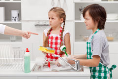 Kids ordered to do the dishes. Grumpy kids ordered to do the dishes - by a parent pointed finger Stock Photos