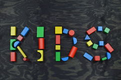 KIDS out of colorful wooden toy blocks on black. The word KIDS out of colorful wooden toy blocks on black wooden background Royalty Free Stock Photos