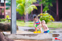 Kids in an outdoor shower. Two happy children, adorable baby boy and a little toddler girl in swimming suits playing in an outdoor shower in a tropical reaost Stock Photos