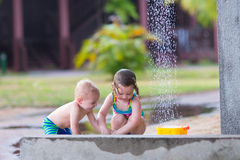 Kids in an outdoor shower. Two happy children, adorable baby boy and a little toddler girl in swimming suits playing in an outdoor shower in a tropical reaost Stock Photo