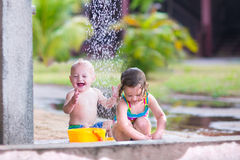 Kids in an outdoor shower. Two happy children, adorable baby boy and a little toddler girl in swimming suits playing in an outdoor shower in a tropical reaost Royalty Free Stock Photo