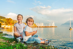Kids  outdoors. Adorable kids having fun outdoors, playing by the lake on a beautiful sunset Stock Photo