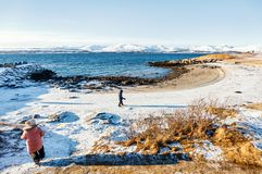 Kids outdoors on winter. Adorable little girl and cute boy enjoying snowy winter day outdoors at beach surrounded by fjords in Northern Norway Stock Photos
