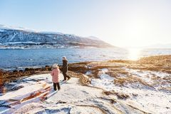 Kids outdoors on winter. Adorable little girl and cute boy enjoying snowy winter day outdoors at beach surrounded by fjords in Northern Norway Royalty Free Stock Photo