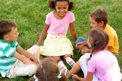 Kids outside. Portrait of cute kids seated on green grass and chatting Stock Image
