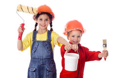 Kids in overalls with paint roller and paintbrush Royalty Free Stock Photography