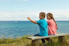 Kids overlooking the ocean. Young caucasian kids in Denmark on a summer day Stock Photos