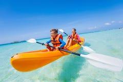 Kids paddling in kayak Stock Photos