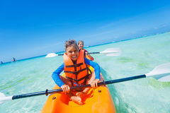 Kids paddling in kayak Stock Photos