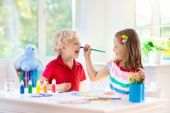 Kids paint. Child painting. Little boy drawing. Kids paint. Child painting in white sunny study room. Little boy and girl drawing rainbow. School kid doing art royalty free stock photo