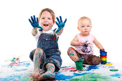 Kids painting. Cute 5 years old boy and toddler girl painting on white background royalty free stock photography