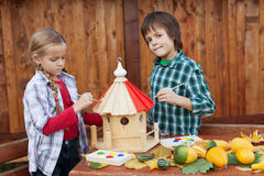 Kids painting a bird house Stock Photo