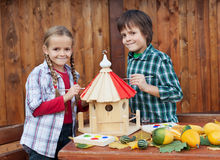 Kids painting the bird house - preparing for winter Stock Photo