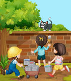 Kids painting brick wall in the garden Stock Image