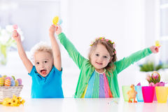 Kids with colorful Easter eggs on egg hunt. Kids painting colorful eggs. Children paint and decorate Easter egg. Toddler kid and preschooler child play indoors stock photos