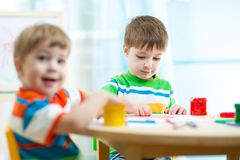 Kids painting in daycare or nursery or playschool Stock Images