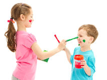 Kids painting faces with paint brushes. Kids making mess painting faces with paint brushes. Isolated on white Royalty Free Stock Photos
