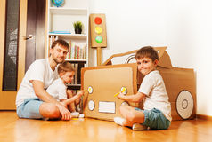 Kids painting headlights on toy cardboard car Royalty Free Stock Image