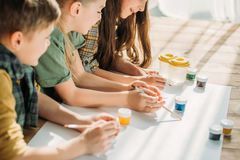 Kids painting on paper with while lying on floor at home Royalty Free Stock Photography