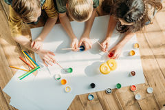 Kids painting on paper with while lying on floor at home Royalty Free Stock Photos