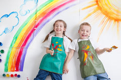 Kids painting rainbow. Two kids smiling and painting rainbow Royalty Free Stock Image