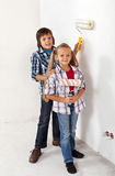 Kids painting their room. With paint rollers - standing together in a new house Stock Image