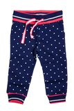 Kids pants isolated. A stylish fashionable dark blue denim trousers with white dots for the little girl. Children sport trousers.  royalty free stock photo