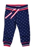 Kids pants isolated. A stylish fashionable dark blue denim trousers with white dots for the little girl. Children sport trousers.  stock photos