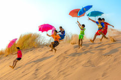 KIDS PARACHUTING OFF SAND DUNES WITH UMBRELLAS Stock Photos