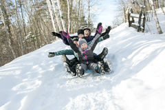 Kids with parents is sledging in winter-landscape. Two kids with parents is sledging in winter-landscape Stock Images