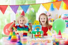 Kids party. Birthday cake with candles for child. Kids birthday party. Child blowing out candles on colorful cake. Decorated home with rainbow flag banners Royalty Free Stock Image