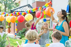 Kids party entertainer letting bubbles. Kids party enetertainer letting soap bubbles during birthday garden party Stock Images