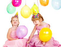 Kids in party hats. Laughing kids in party hats playing with birthday balloons stock images