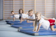 Kids improving coordination and balance at school. Kids performing exercises to improve their motor skills, coordination and balance royalty free stock image