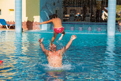 Kids having fun in the swimming pool. Teenager and little girl performing martial arts lesson in outdoor swimming pool Stock Photo