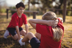 Kids performing stretching exercise during obstacle course. In boot camp stock image