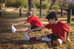 Kids performing stretching exercise during obstacle course stock photography