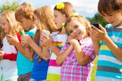 Kids with phones Royalty Free Stock Photo