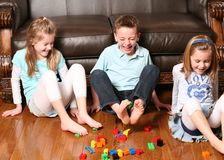 Kids pickup up blocks with feet. Three childrens playing with blocks with their feet Royalty Free Stock Image