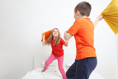 Kids pillow fight. Kids having a pillow fight in bed royalty free stock photo