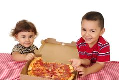 Kids and pizza. Hispanic boy and girl two and three years old ready to eat a take-out pepperoni pizza, on white background Royalty Free Stock Photography