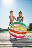 Kids plalying with a beach ball on a pier Stock Photo