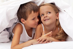 Kids planning the next prank. Hidden under the quilt Stock Images