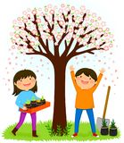 Kids planting saplings under a blooming tree Stock Image