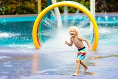 Kids at aqua park. Child in swimming pool. Kids play in aqua park. Children at water playground of tropical amusement park. Little boy at swimming pool. Child royalty free stock image