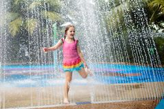 Kids play in aqua park. Children at water playground of tropical amusement park. Little girl at swimming pool. Child playing at. Water slide on summer vacation stock images
