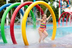 Kids at aqua park. Child in swimming pool. Kids play in aqua park. Children at water playground of tropical amusement park. Little girl at swimming pool. Child stock images